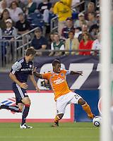 Houston Dynamo midfielder Corey Ashe (26) dribbles as New England Revolution midfielder Chris Tierney (8) pressures. The New England Revolution defeated Houston Dynamo, 1-0, at Gillette Stadium on August 14, 2010.