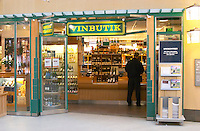 The sign in front of one of the Systembolaget shops. Systembolaget is the monopoly alcohol wine beer spirit retailer in Sweden. This store only sells wine according to the sign saying vinbutik (Wine Shop). Shelves with bottles on display. A customer waiting at the delivery counter. You have to ask the shop staff to go and get the bottle. Stockholm, Sweden, Sverige, Europe