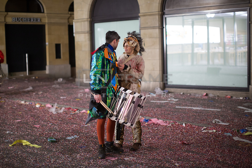 Two costumed participants in the Carnival of Basel or Fasnacht, take a moment on a confetti-covered road in the old town of Basel, Switzerland. Feb. 26, 2015.