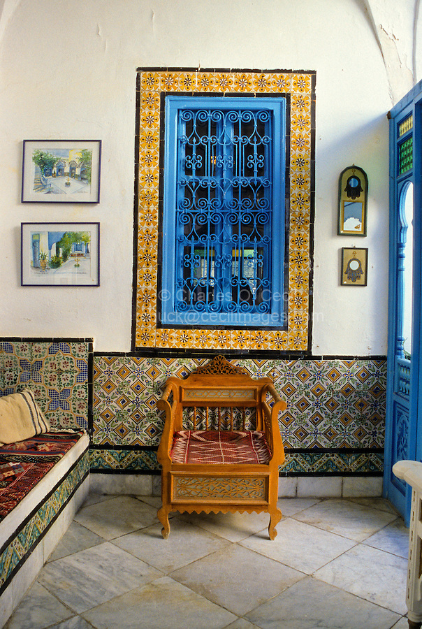 """Tunisia, Sidi Bou Said.  Reception Room of Dar Annabi, a Private Home open for Public Viewing.  Originally constructed 18th. century, remodeled 20th. century.  Inner reception rooms are reserved for family and close friends.  Yellow, black, and white """"lion's paw"""" tiles around the window."""