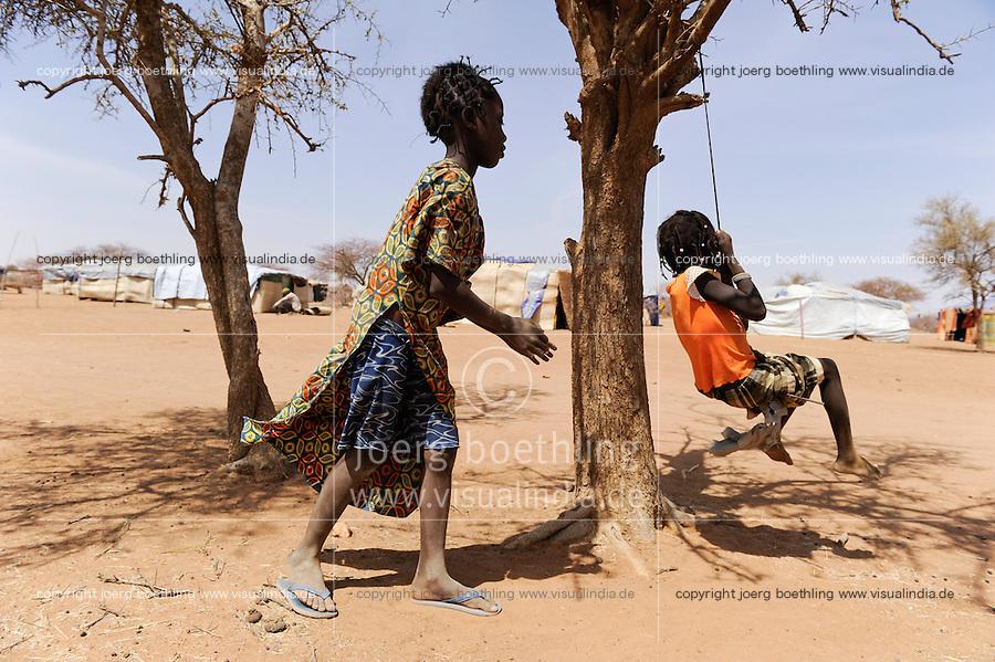 BURKINA FASO Dori , malische Fluechtlinge, vorwiegend Tuaregs, im Fluechtlingslager Goudebo des UN Hilfswerks UNHCR, sie sind vor dem Krieg und islamistischem Terror aus ihrer Heimat in Nordmali geflohen, Kinder schaukeln an einem Baum / BURKINA FASO Dori, malian refugees, mostly Touaregs, in refugee camp Goudebo of UNHCR, they fled due to war and islamist terror in Northern Mali, children swing on tree