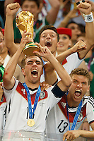 Philipp Lahm of Germany celebrates winning the FIFA World Cup by lifting the trophy with his team mates and Thomas Muller