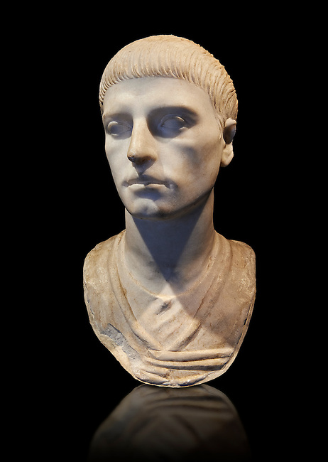 Roman portrait bust of a young man from the rule of Trajan 98-117 AD. This bust of a man presents a hairstyle with long curls that are closely cut to the head and cover the forehead with a thick fringe that follows the shape of the face. The style comes from the official portraits of Trajan, 97-117 AD, created for his Decennalia, celebrating the tenth year of his reign. Inv 317, The National Roman Museum, Rome, Italy