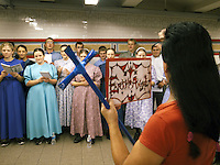 """USA. New York City. Union Square. Subway station. Unexpected religious encounteer betweeen a group of Mennonites singing and proselytizing, and a man calling himself """"The Angel"""", who carries a blue catholic cross in his hands. Mosaic tiles on wall. 22.10.2011 © 2011 Didier Ruef"""