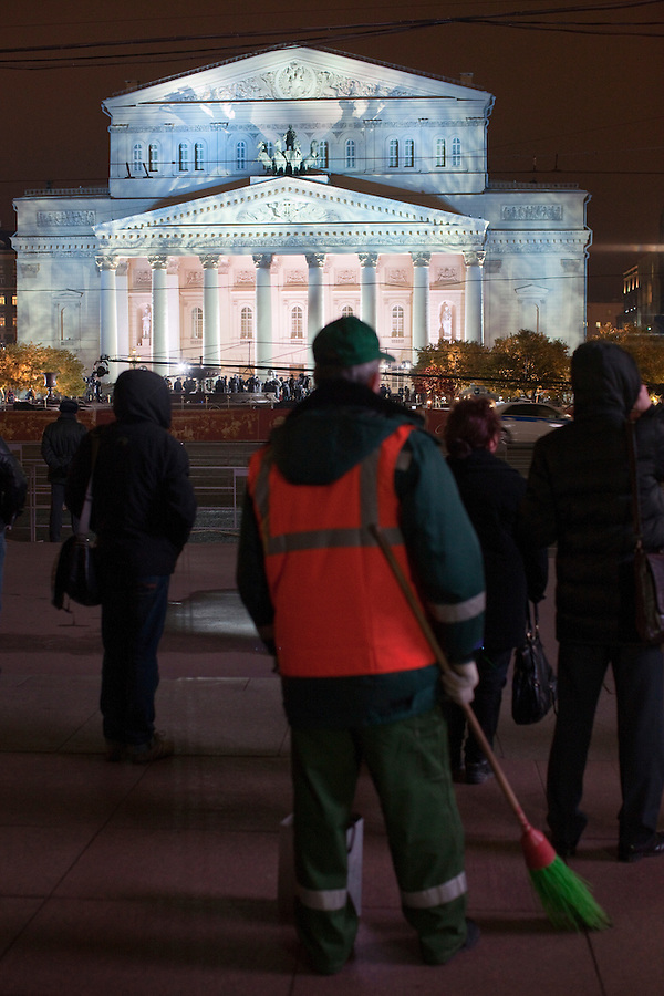Moscow, Russia, 28/10/2011..A street cleaner looks at the Bolshoi Theatre floodlit for its gala reopening. The theatre had been closed since 2005 for reconstruction work that cost some $700 million.