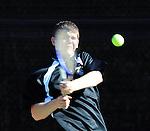 Tennis player swings a hard backhand.