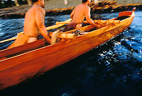 Two Hawaiian men pulling an outrigger fishing canoe ashore