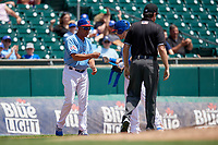 Buffalo Bisons manager Bob Meacham (10) fist bumps Billy McKinney (11) after hitting a triple during an International League game against the Lehigh Valley IronPigs on June 9, 2019 at Sahlen Field in Buffalo, New York.  Umpire John Bacon gets back into position.  Lehigh Valley defeated Buffalo 7-6 in 11 innings.  (Mike Janes/Four Seam Images)