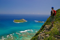 A hiker stops to enjoy a panoramic view of Manana (Rabbit) Island, Kaohikaipu (Black or Bird) Island and Kaupo (or Cockroach) Bay from Tom-Tom Trail above Sea Life Park along the Windward Oahu coast.