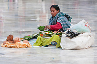 India, Rishikesh.  Woman Preparing Offerings to Sell to Early-morning Worshippers at the River Ganges (Ganga).