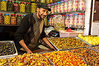 Fes, Morocco.  Olive Vendor Talking to a Customer in the Medina.