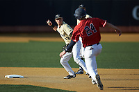Wake Forest Demon Deacons shortstop Bruce Steel (17) prepares to make a throw to first base as Ben Highfill (24) of the Liberty Flames hustles towards second base at David F. Couch Ballpark on April 25, 2018 in  Winston-Salem, North Carolina.  The Demon Deacons defeated the Flames 8-7.  (Brian Westerholt/Four Seam Images)