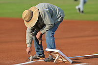 One of the members of the grounds crew sets first base as the Ogden Raptors get ready to take on the Helena Brewers at Lindquist Field in Pioneer League play on July 23, 2013 in Ogden Utah. (Stephen Smith/Four Seam Images)