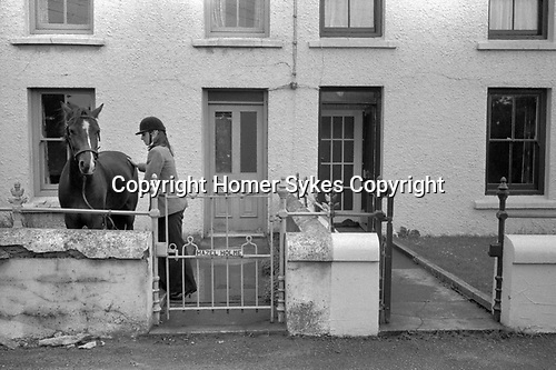 Douglas, Isle of Man, young girl with her horse saddling up in front of her home 1970s 1978