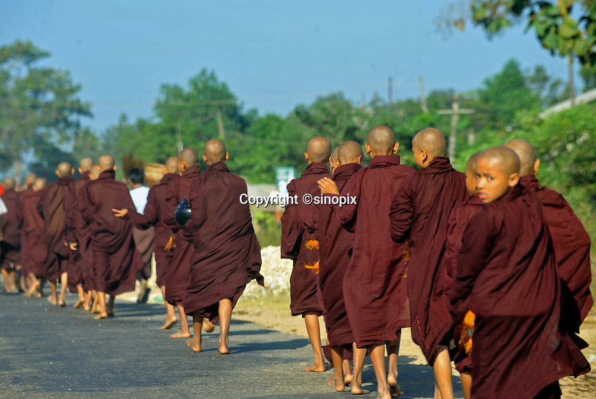 Monks walk in the coutryside along the  Rangoon-Mandalay Road , Burma Nov 2008.  Monks in this largely Buddhist country have to beg from villagers in order to feed themselves.<br /> <br /> Photo by Richard Jones