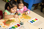 Education preschool 3 year olds art activity two girls water color painting one using right hand the other the left hand