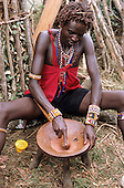 Lolgorian, Kenya. Young Moran Siria Maasai using a pestle to crush ochre in a three-legged wooden mortar for body painting
