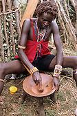Lolgorian, Kenya. Young Moran Siria Maasai using a pestle to crush ochre in a three-legged wooden mortar for body painting