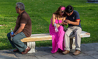 Peru, Lima.  Couple Checking Cell Phone, Plaza de Armas.