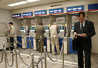 People queue at automatic teller machines (ATM's) in a bank in Tokyo banking and business district called Otemachi..