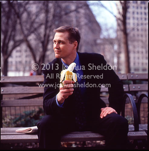 Out of focus man in suit sitting on park bench holding a banana<br />