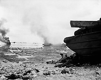 An amphibious tractor burns on the beach as Marines take shelter under a duck.  Peleliu, September 1944.  Pfc. John J. Smith. (Marine Corps)<br /> Exact Date Shot Unknown<br /> NARA FILE #:  127-N-95249<br /> WAR & CONFLICT BOOK #:  1178
