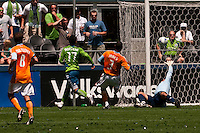 Fredy Montero of the Seattle Sounders scores overe Pat Onstad of the Houston Dynamo in the match at the XBox Pitch at Quest Field on July 11, 2009. The Sounders defeated the Dynamo 2-1.