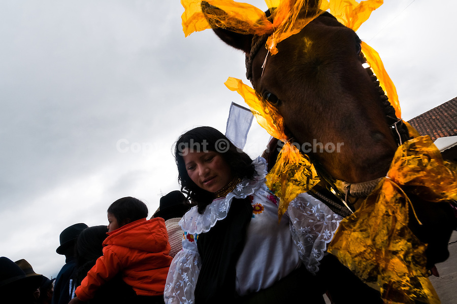 """A woman holds a colorfully decorated horse during the Inti Raymi celebration in Pichincha province, Ecuador, 26 June 2010. Inti Raymi, """"Festival of the Sun"""" in Quechua language, is an ancient spiritual ceremony held in the Indian regions of the Andes, mainly in Ecuador and Peru. The lively celebration, set by the winter solstice, goes on for various days. The highland Indians, wearing beautiful costumes, dance, drink and sing with no rest. Colorful processions in honor of the God Inti (Sun) pass through the mountain villages giving thanks for the harvest and expressing their deep relation to the Mother Earth (Pachamama)."""