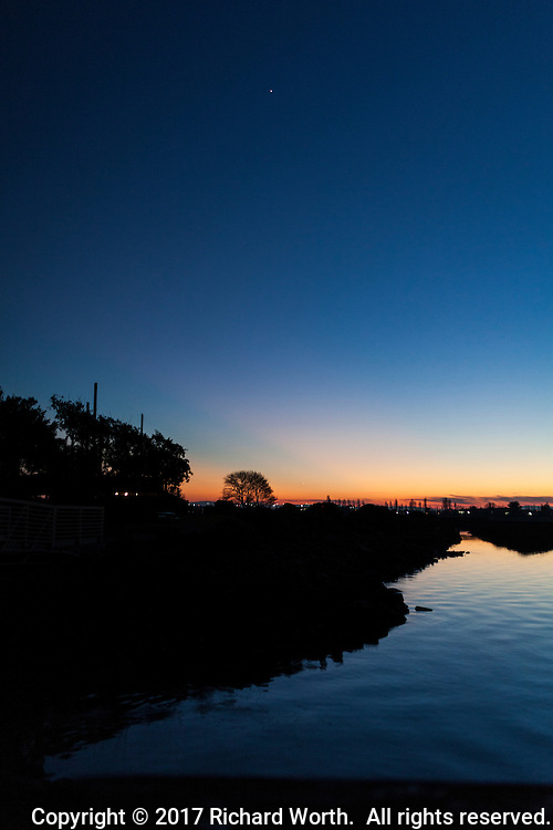 Venus floats in a clear blue sky at sunset over the waters along Martin Luther King Jr. Regional Shoreline in Oakland, CA, on Martin Luther King Day 2017