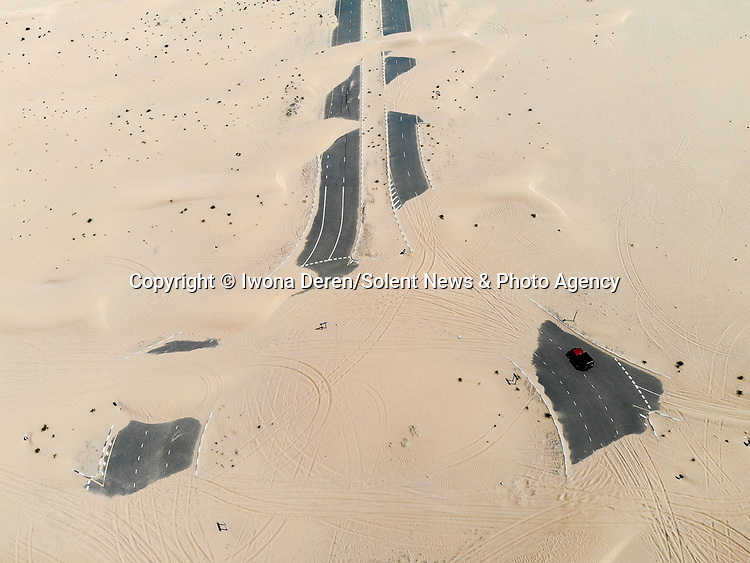 """Pictured: Desert roads lie almost completely hidden - as aerial images show them being swallowed up wind-blown sand.   Just a single car can be seen trying to cross the tarmac near Dubai as the surrounding dunes threaten to cover them up entirely.<br /> <br /> The striking photos were captured by Polish airline worker Iwona Deren who had travelled to the United Arab Emirates to practice off road driving in the desert.   """"Pretty much all roads in the UAE, especially those in the middle of the desert need to be maintained constantly to remove the sand blowing from the dunes nearby,"""" the 30 year old said.   SEE OUR COPY FOR DETAILS<br /> <br /> Please byline: Iwona Deren/Solent News<br /> <br /> © Iwona Deren/Solent News & Photo Agency<br /> UK +44 (0) 2380 458800"""