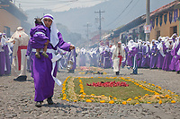 Antigua, Guatemala. Incense fills the air as cucuruchos in purple tunics prepare the way for a religious procession during Holy Week, La Semana Santa.   An alfombra (carpet) of flowers, pine needles, and other traditional materials decorates the street.  It will only exist for an hour or two before the procession walks over it, after which the remains will be quickly cleaned up by municipal street cleaners.