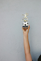 Young footballer holds trophy aloft after wininng final