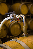 Grape juice is pumped from one OAK BARREL to another to remove sediment at JOULLIAN VINEYARDS - CARMEL VALLEY, CALIFORNIA