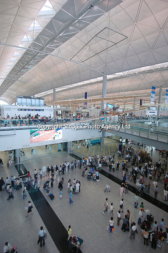 Chek Lap Kok Airport, Hong Kong .Passengers gather under a model of an historic biplane in the passenger terminal of Hong Kong's Chek Lap Kok airport..16-JUL-04