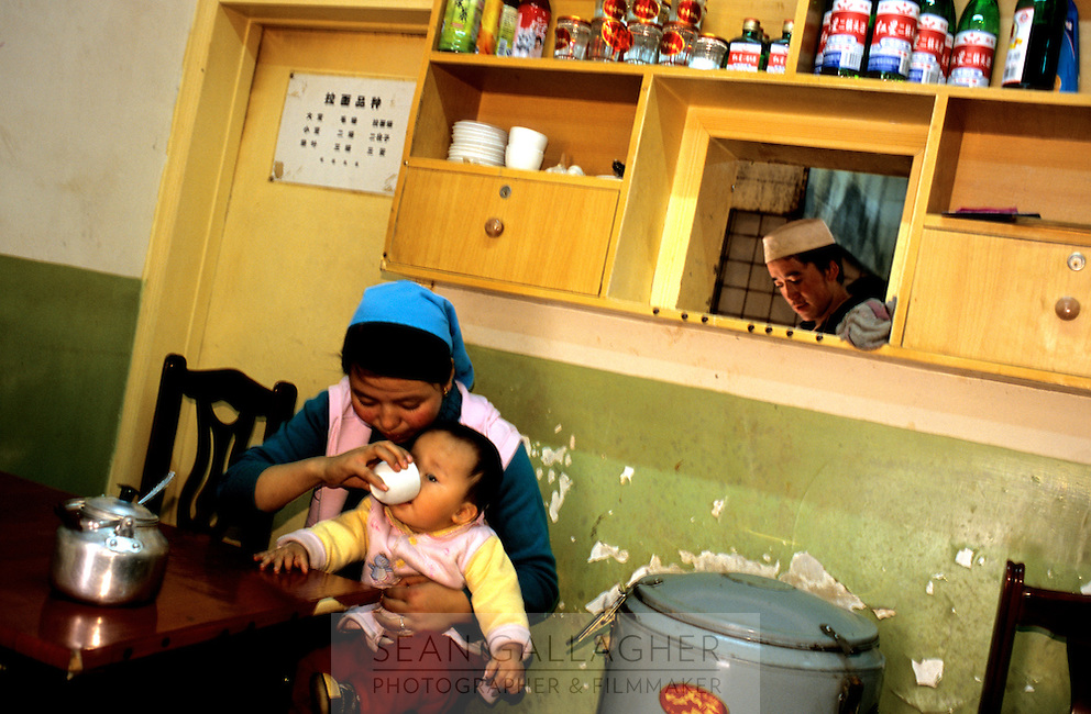 CHINA. Beijing. A young Muslim family in their restaurant. 2005