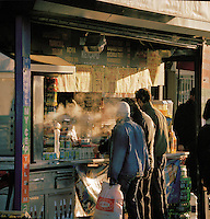 Men buying food from a street vendor early in the morning in Istanbul, Turkey