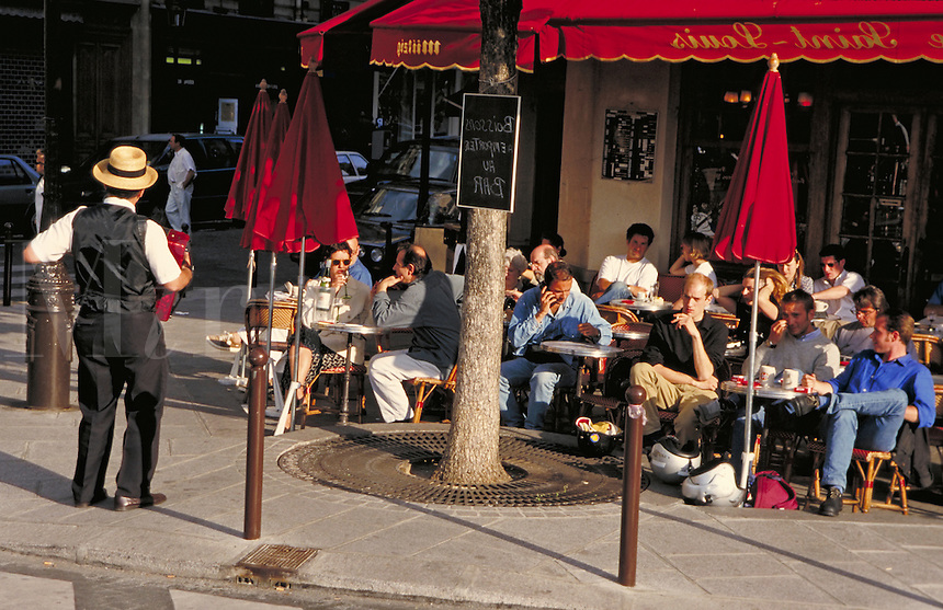 A street musician performs for a cafe crowd in Paris, France. occupations, performers, street scene. Paris, France.