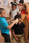Education preschool 4-5 year olds pretend play group of boys and girls playing hairdresser or barber shop cutting and styling hair of classmates