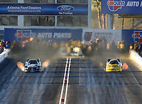 Feb 21, 2014; Chandler, AZ, USA; NHRA funny car driver Cruz Pedregon (left) races alongside Jeff Arend during qualifying for the Carquest Auto Parts Nationals at Wild Horse Pass Motorsports Park. Mandatory Credit: Mark J. Rebilas-USA TODAY Sports