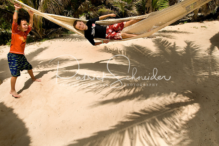 Two boys play with a hammock on a sandy beach near Cancun, Mexico.