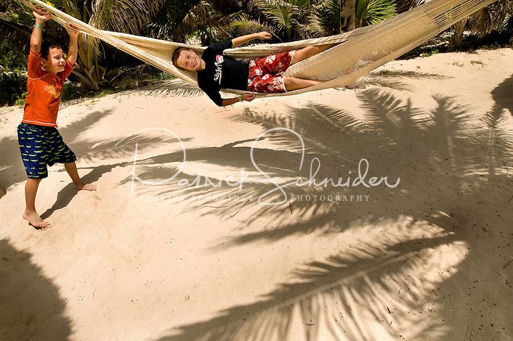 Two boys play with a hammock on a sandy beach near Cancun, Mexico.