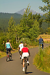 Family riding bikes on paved path, Central Oregon