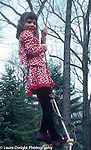 6 year old girl outside climbing on rope swing