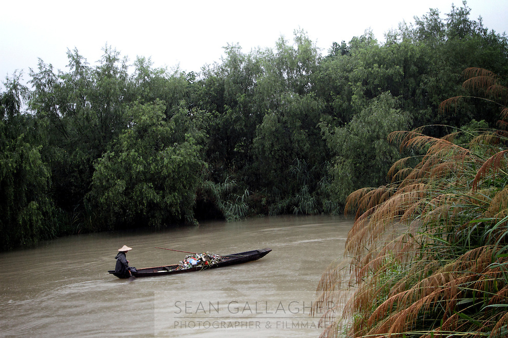 A man paddles a boat used for collecting rubbish in the Xixi wetlands which lie in the west of the city of Hangzhou. This is China's 'first national wetland park,' dubbed as such to act as a role model to all other wetlands in China and to supposedly show how to effectively manage and restore wetlands, notably urban wetlands. Zhejiang Province. China. 2010
