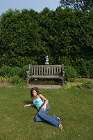 Woman laying on grass with bench in background