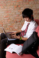 Montreal (Qc) CANADA , October 2007 -<br /> Model Released photo -<br /> 17 year half asian-half white EMO teenager<br /> using a laptop computer with wifi internet to do his homework and surf the net.<br /> photo : (c) images Distribution