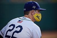 Savannah Bananas Ryan Kennedy (22) wears a mask, while sitting outside the dugout to practice social distancing, during a Collegiate Summer League game against the Macon Bacon on July 15, 2020 at Grayson Stadium in Savannah, Georgia.  (Mike Janes/Four Seam Images)