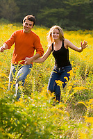 Couple running through field of goldenrod