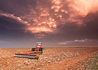 Orange & purple supercell thunderstorm w/ mammatus clouds above a tractor at sunset in Grady, NM, June 12, 2012