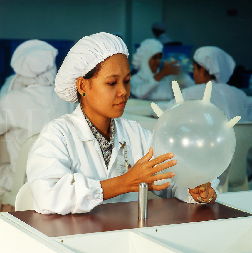 Girl testing surgical glove in modern manufacturing plant. West Malaysia..